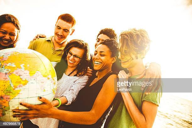 Grupo de amigos sosteniendo un globo de tierra