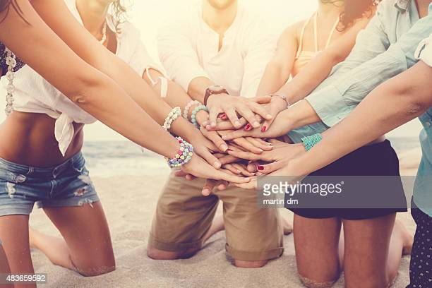 Group of friends holding hands together to show solidarity