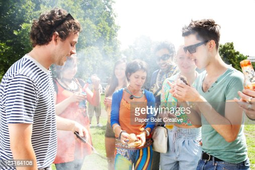 group of friends huddled around a bbq grill : Foto stock