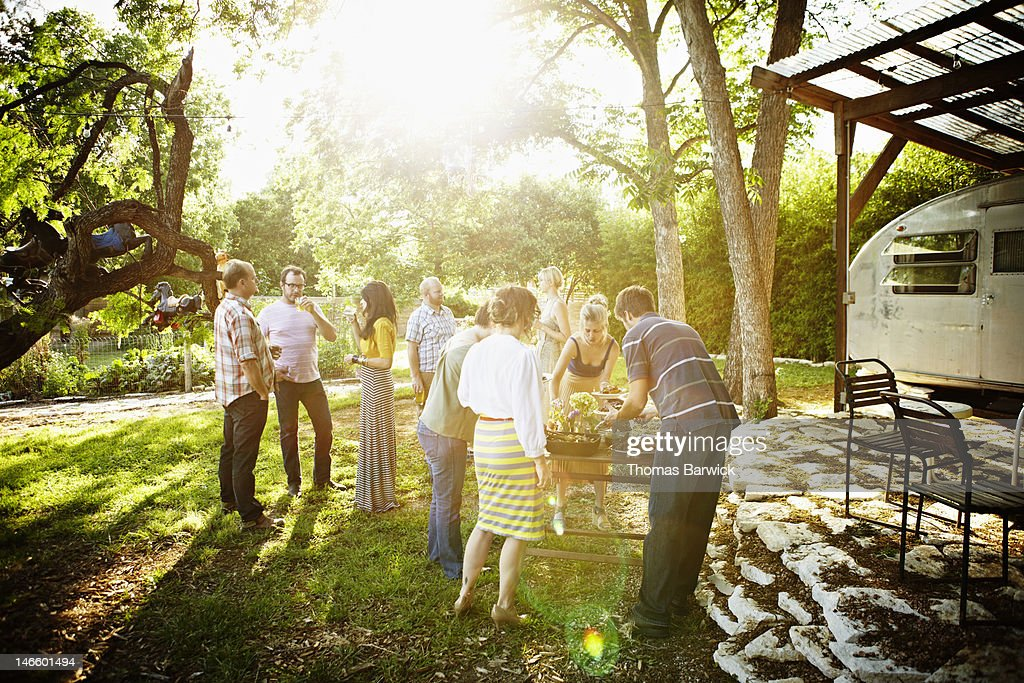 Group of friends in backyard dishing up food : Stock Photo