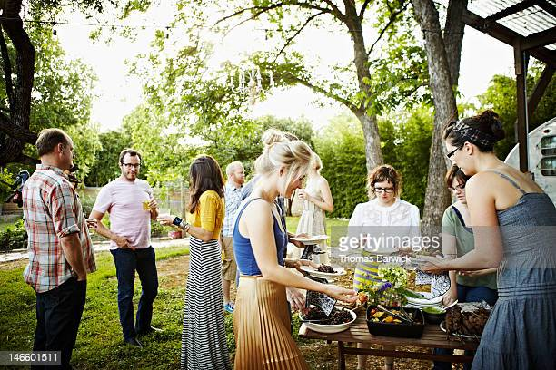 Group of friends in backyard dishing up food