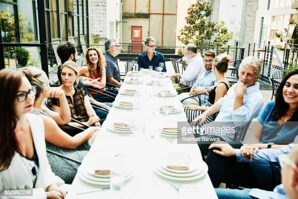Group of friends in discussion while seated for celebration meal at table on outdoor patio
