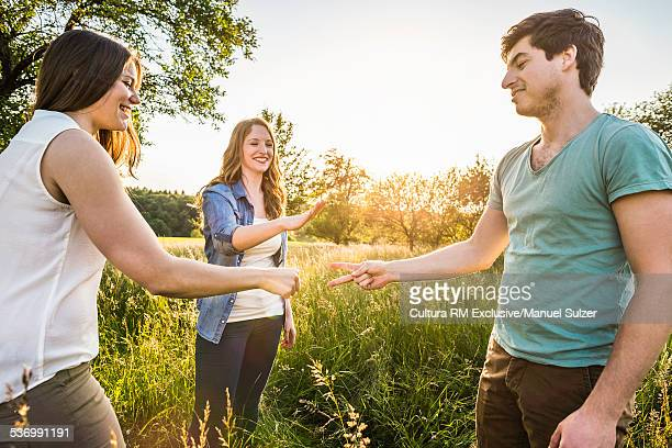 Group of friends in field playing scissors, paper, stone