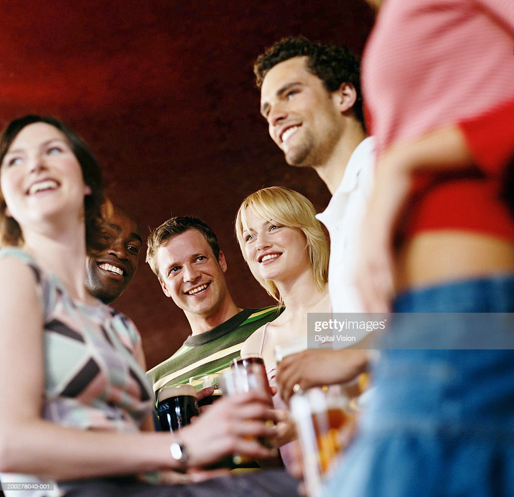 Group of friends in pub holding drinks, smiling, low angle view : Stock Photo