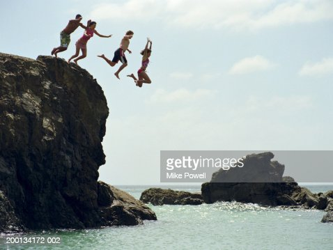 Group of friends jumping into ocean from rock cliff : Stock Photo