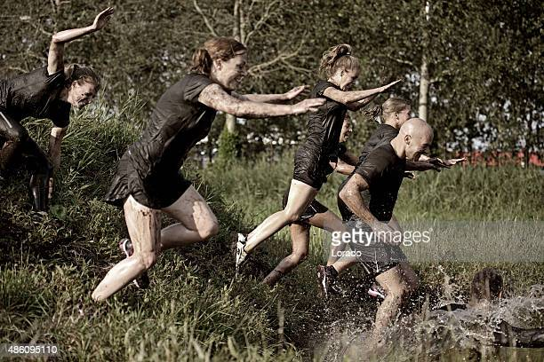 group of friends jumping into water during mud run