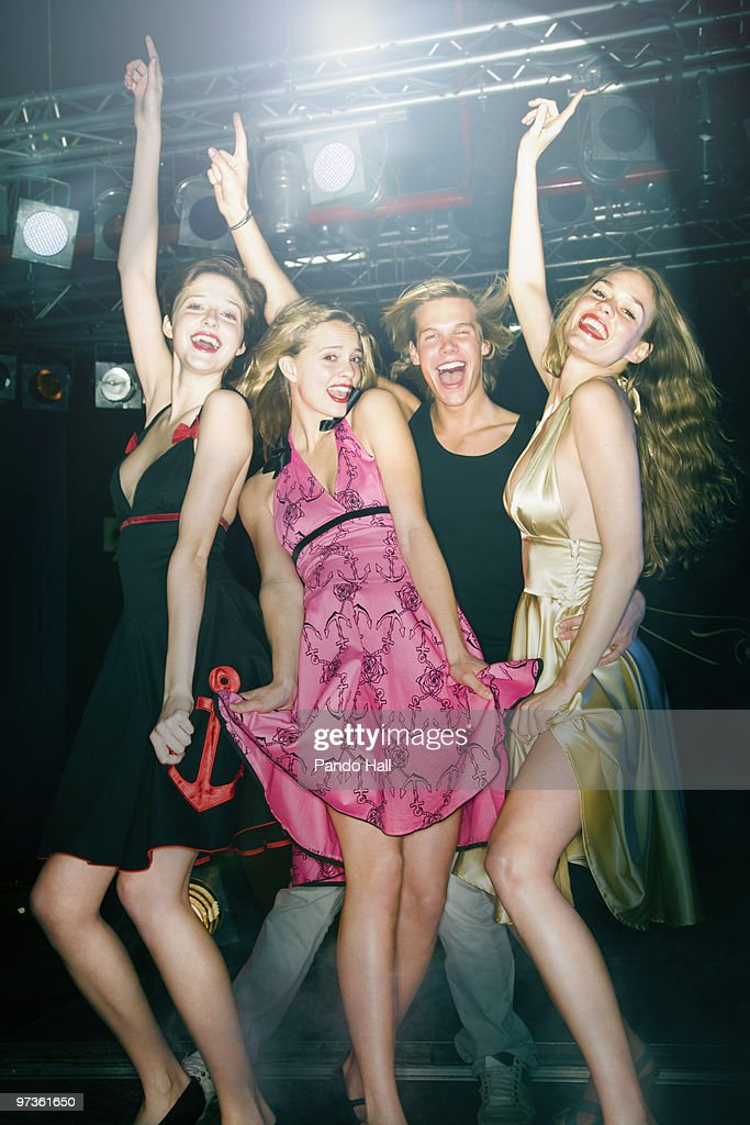 Group of friends laughing and dancing in nightclub : Stock Photo