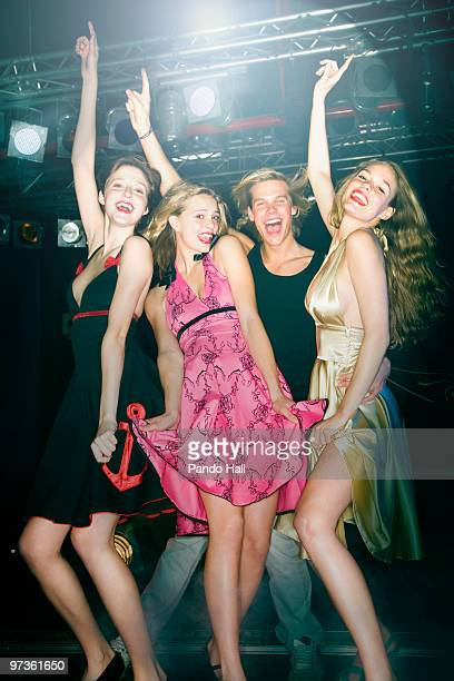 Group of friends laughing and dancing in nightclub