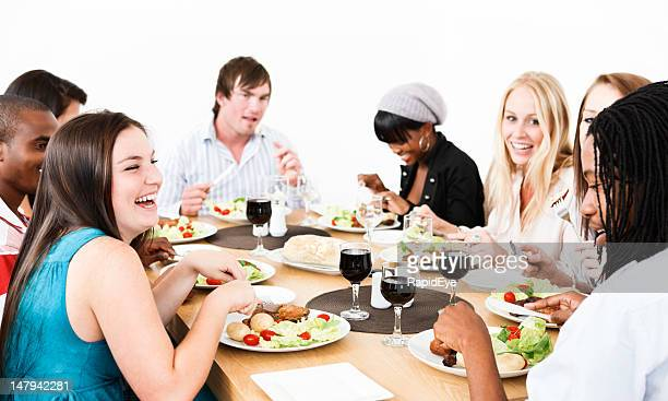 Group of friends laughing and eating dinner