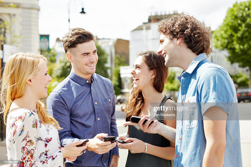 Group of friends laughing with smart phones. : Stock Photo