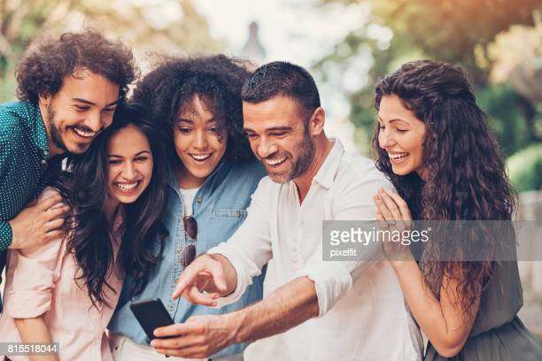 Group of friends looking at a smart phone