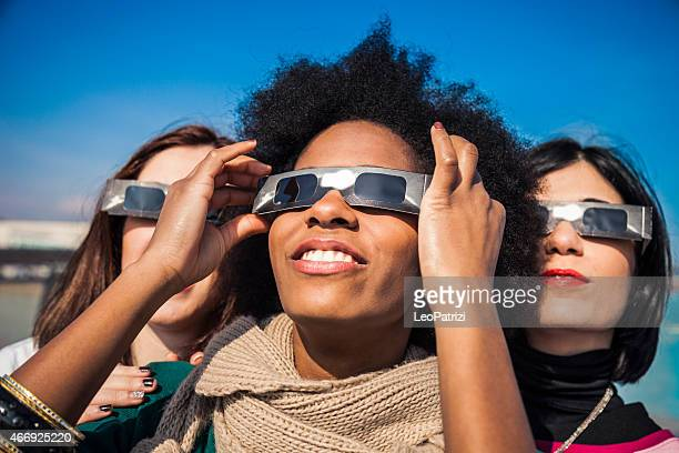 Group of friends looking to a solar eclipse