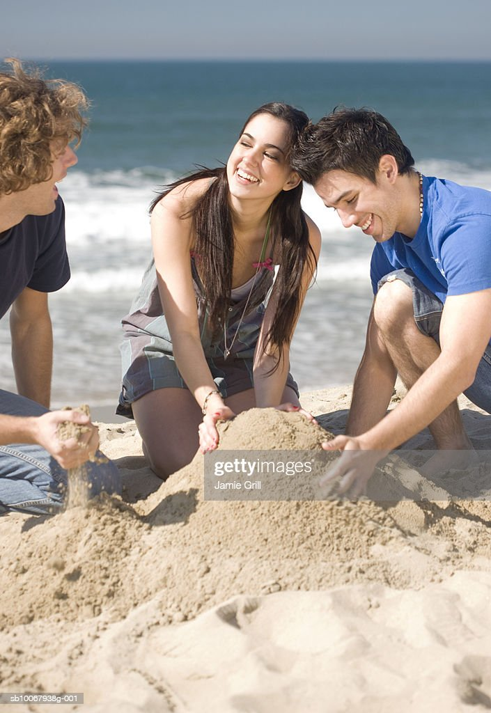 Group of friends making sandcastle on beach