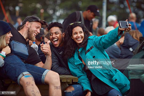 Group of friends making selfie at festival