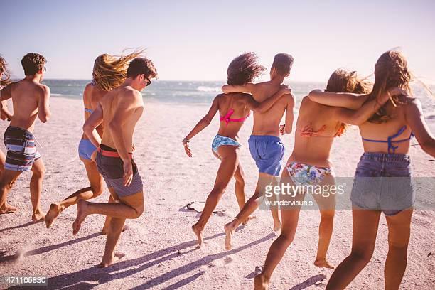 Groupe d'amis de course courses variés ensemble sur la plage