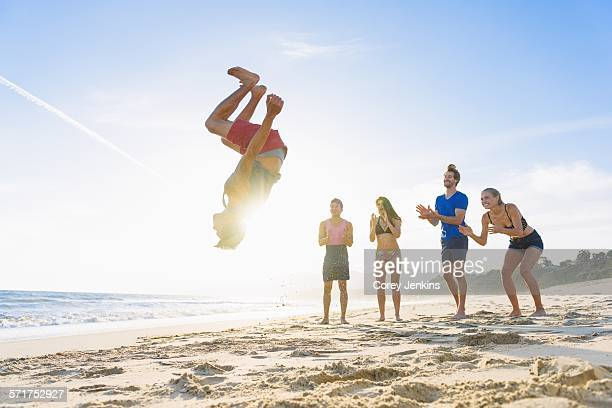 Group of friends on beach watching friend do somersault