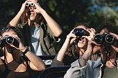 Group of friends on off road vehicle with binoculars