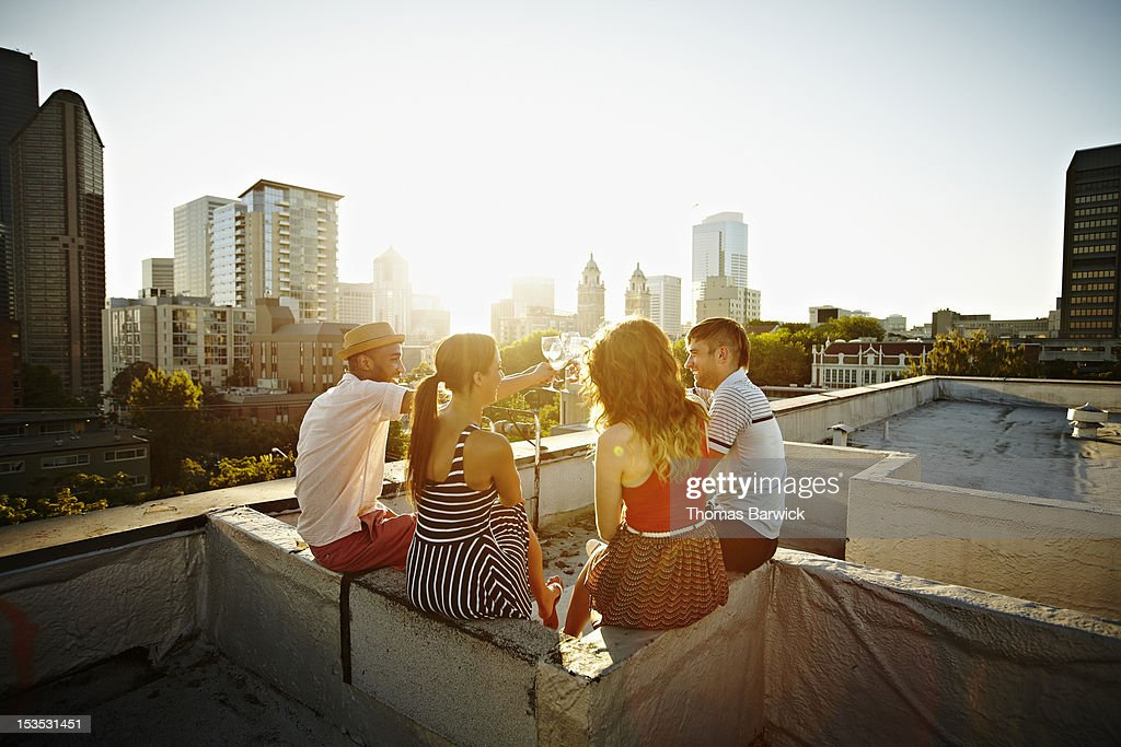 Group of friends on roof toasting at sunset : Stock Photo