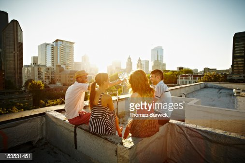 Group of friends on roof toasting at sunset : ストックフォト