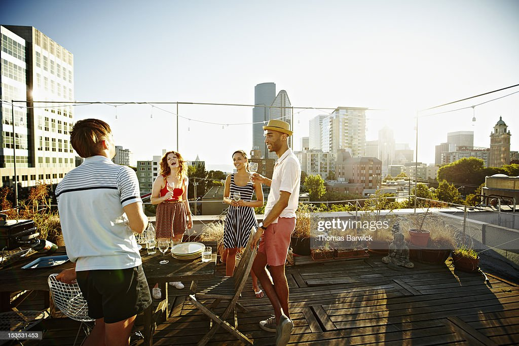 Group of friends on rooftop deck at sunset : Stock Photo