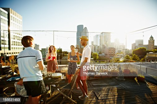 Group of friends on rooftop deck at sunset : Foto de stock
