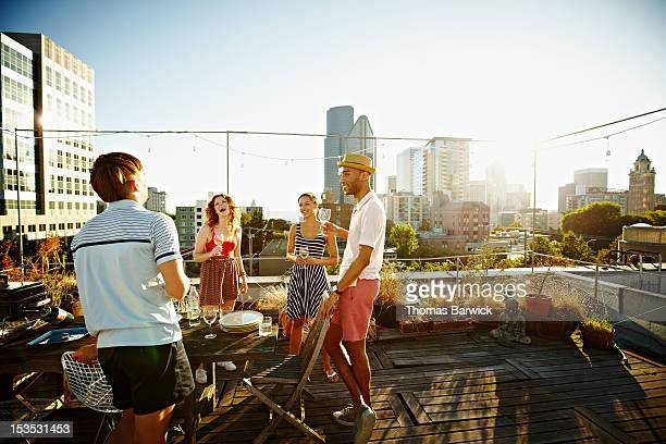Group of friends on rooftop deck at sunset
