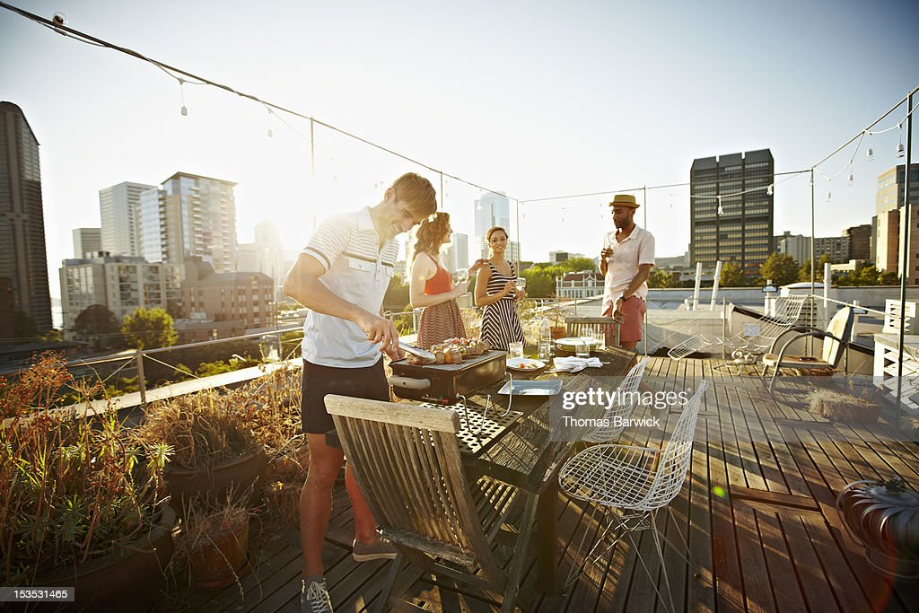 Group of friends on rooftop deck cooking dinner : Stock Photo