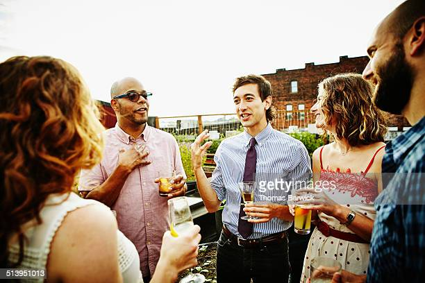 Group of friends on rooftop deck on summer evening