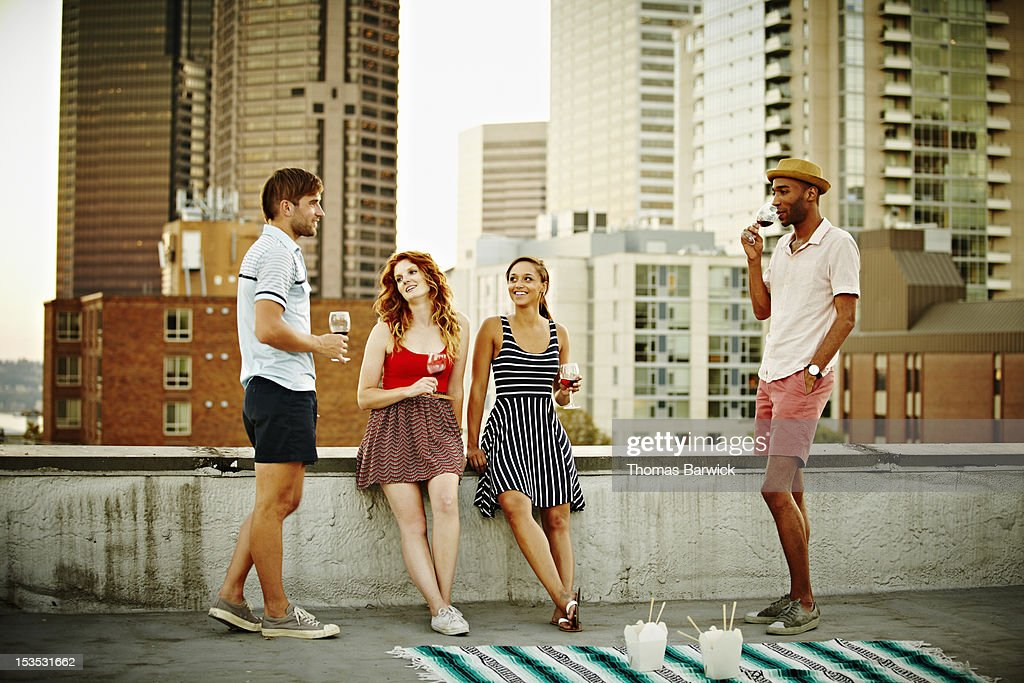 Group of friends on rooftop talking and drinking : Stock Photo