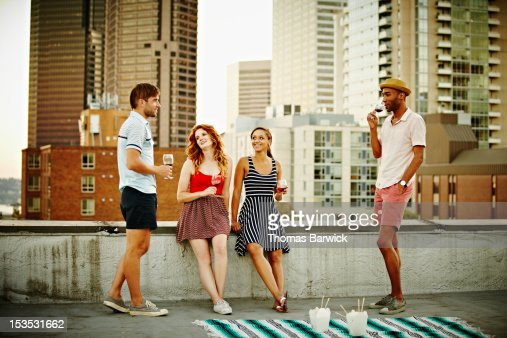 Group of friends on rooftop talking and drinking