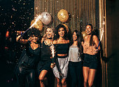 Shot of group of young women celebrating new years eve at the pub. Group of female friends with sparklers partying in nightclub.