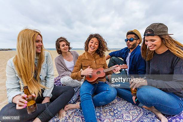 Group of Friends Partying on a Beach Playing Music