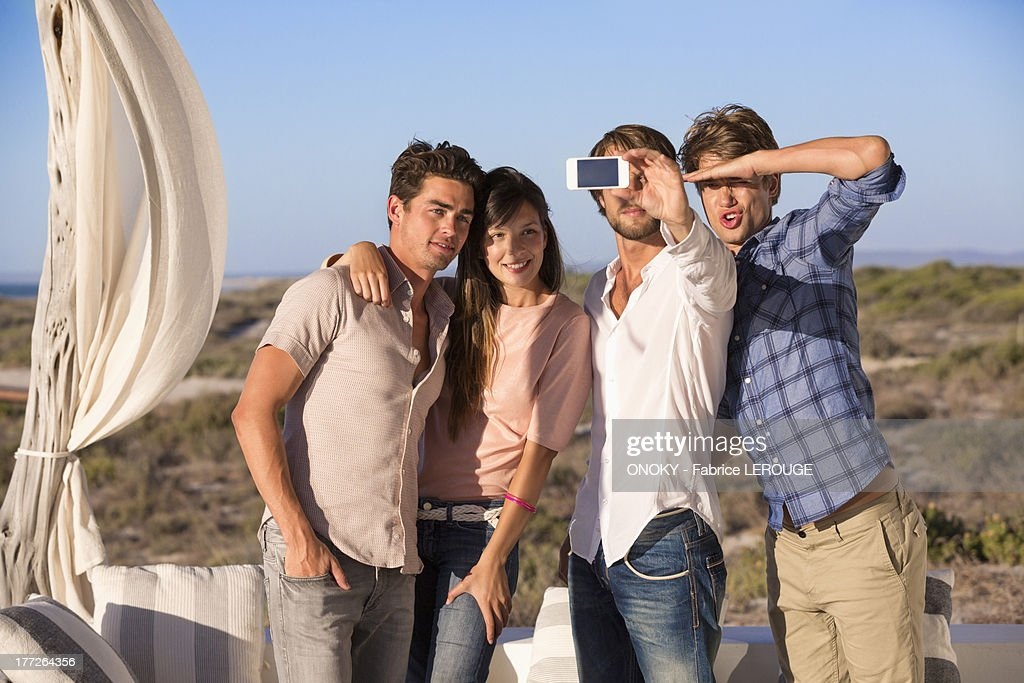 Group of friends photographing themselves with a mobile phone : Stock Photo