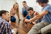 A group of friends play board games on the floor having fun at a party indoors.