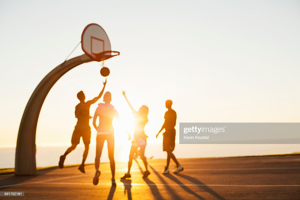 Group of friends playing basketball, outdoors