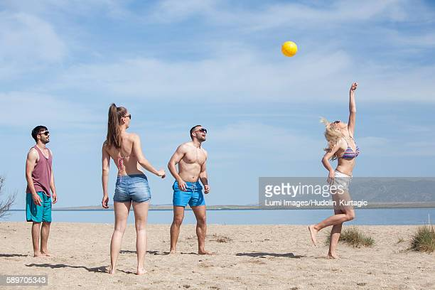 Group of friends playing beach volleyball
