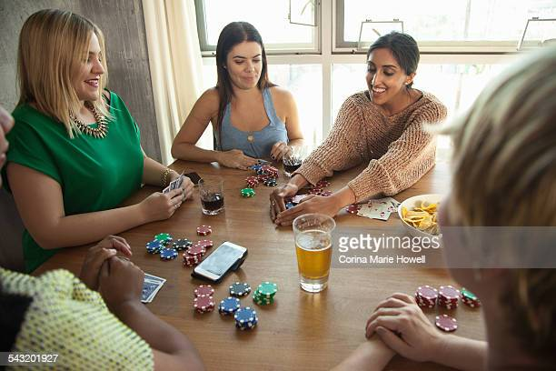 Group of friends playing cards around table
