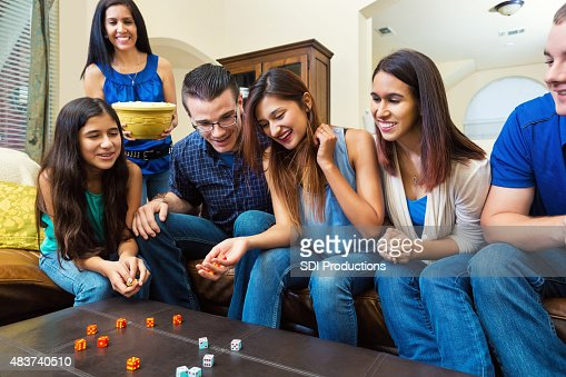 Family Laughing While Playing Game Together In Living Room Stock