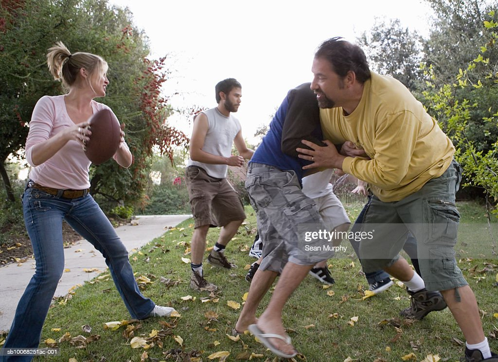 Group of friends playing football in park : Stock Photo