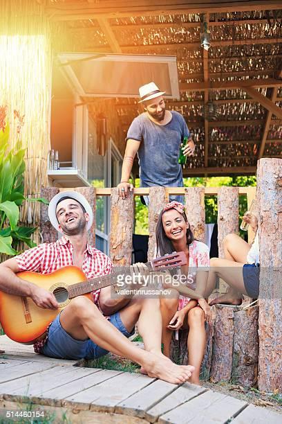 Group of friends playing guitar at veranda