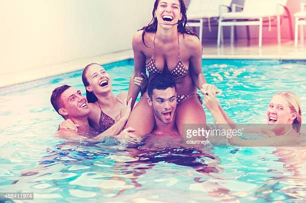 Groupe d'amis jouant dans la piscine.