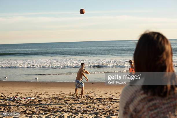 Group of friends playing on beach with ball