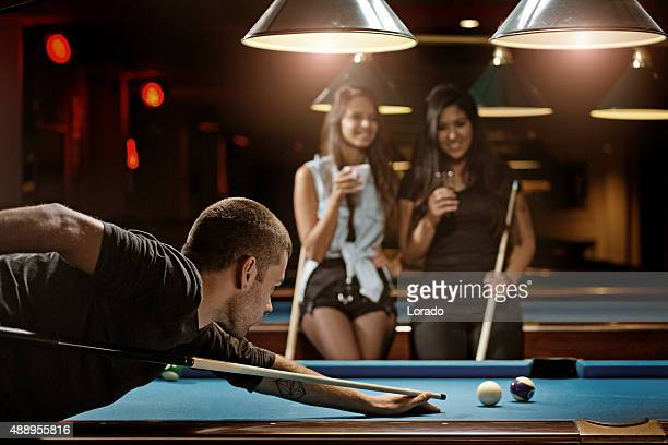 Group of friends playing pool in a local pool hall