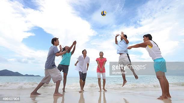 Groupe d'amis jouer au volley-ball sur la plage.