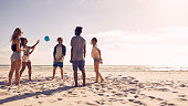 Group of friends playing with ball at beach on a summer day. Young men and woman on sandy beach playing a game of passing the ball.