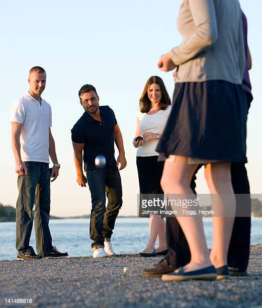 Group of friends playing with boule beside sea