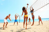 Activity on the beach - A large group of friends plays volleyball on the sand.
