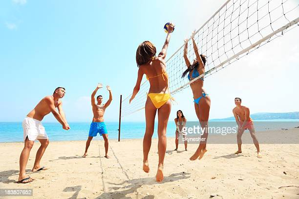 Group of friends plays volleyball on the beach.