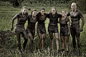 group of friends posing together after mud obstacle