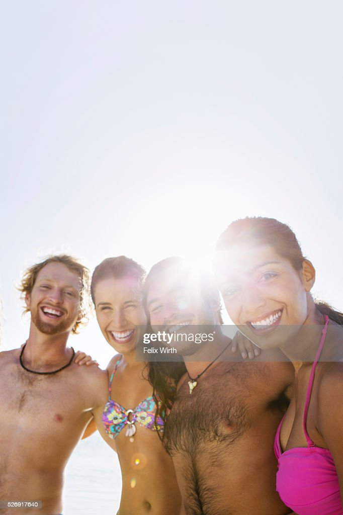 Group of friends posing together on sandy beach : Stockfoto